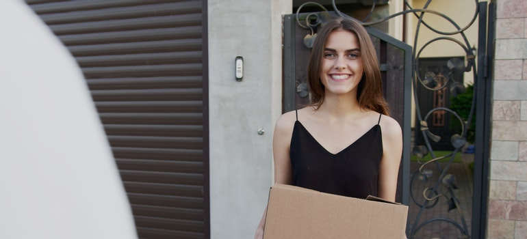A happy woman holding a box