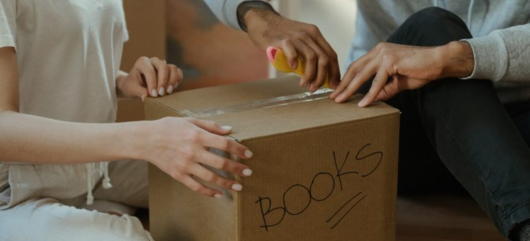 "Two people packing a box labeled ""Books""."