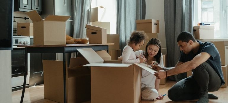 a family sitting surrounded by moving boxes