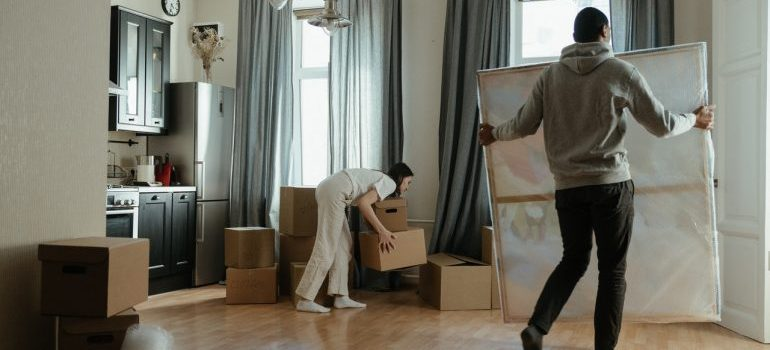 Two people packing and unpacking a room for relocation.