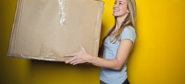 A happy woman carriying a moving box.
