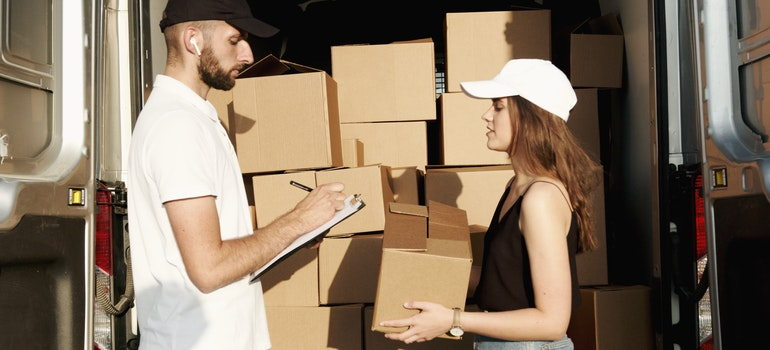 A woman doing business with professional Belmont movers behind a moving truck