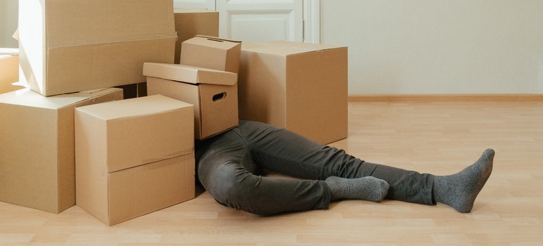 A man coveredin moving boxes because he's exhausted from moving preparations.