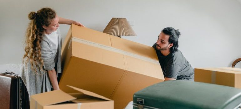 a couple trying to lift a moving box, representing reasons to hire Chelsea movers