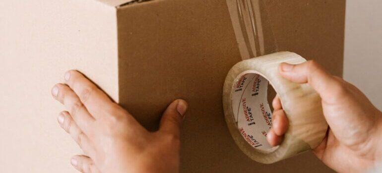 a man packing a box, representing astoria ny moving companies