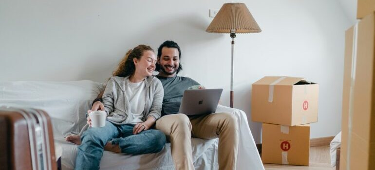 Young couple using laptop to find out details about moving from NYC to California.