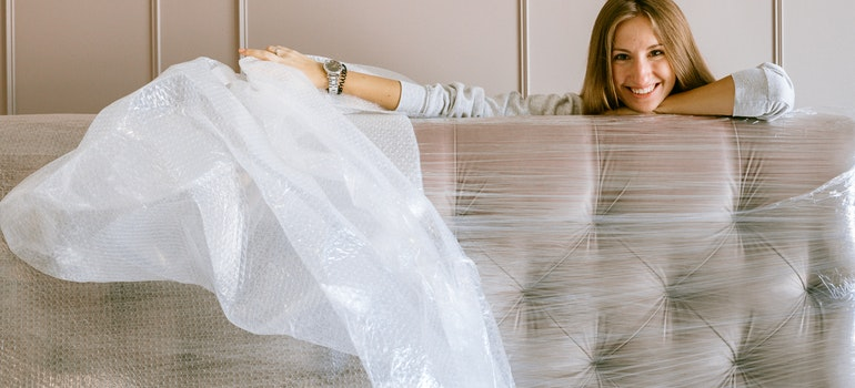 A woman unpacking a couch.