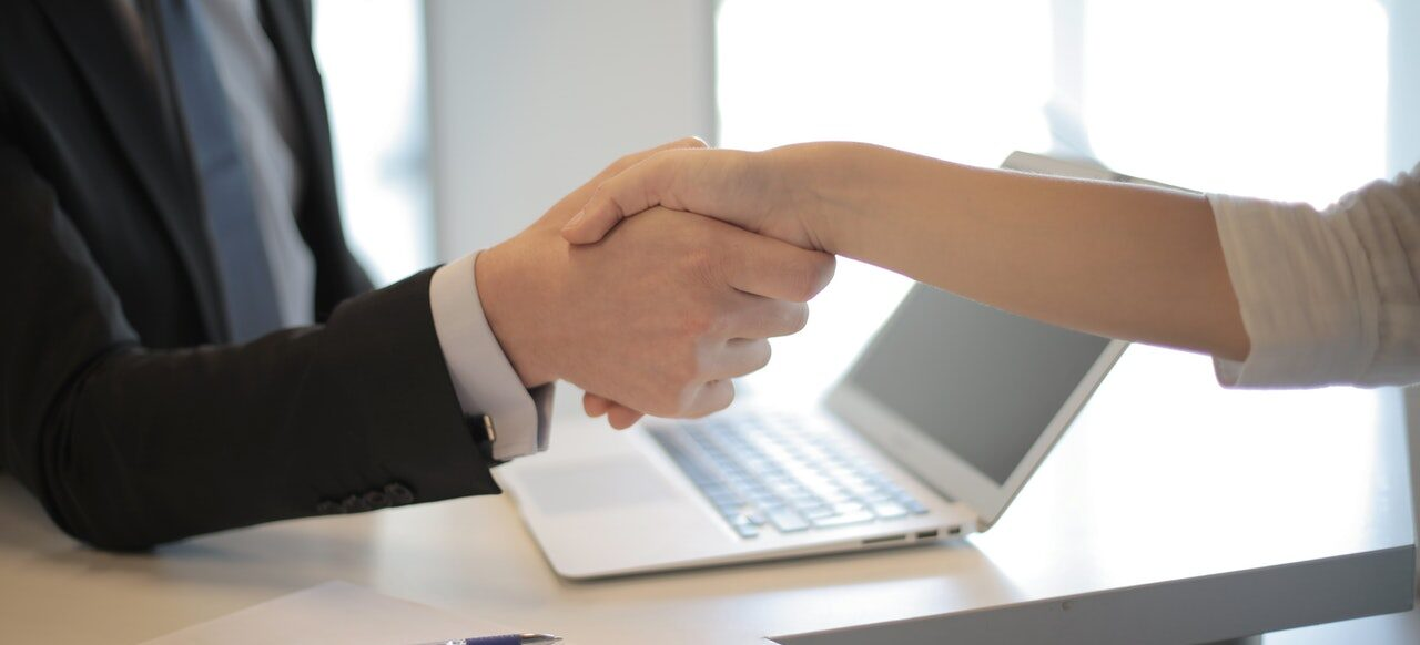An emplyee and a client shaking hands.