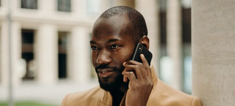 A man in a brown coat talking on the phone.