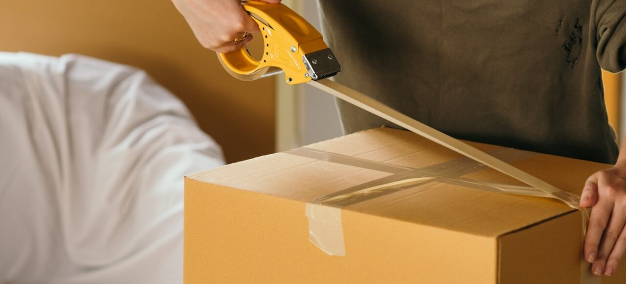 A mover taping a box.