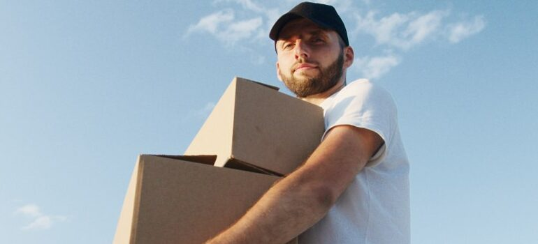 male in a white shirt carrying moving boxes