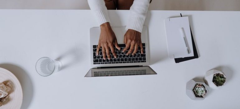 A woman typing something on a white laptop on a white table, in search for Mount Hope movers.