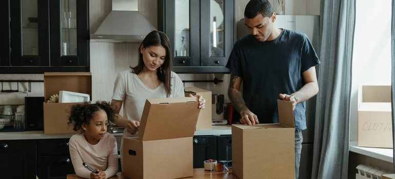 A family packing items into cardboard boxes.