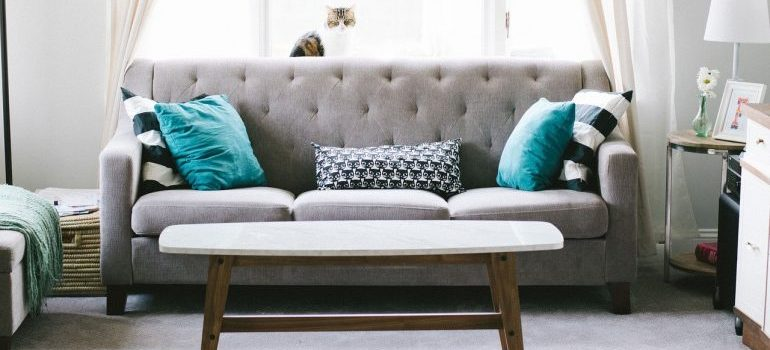 A gray couch with teal pillows, representing furniture moved by movers in Elmhurst NY.