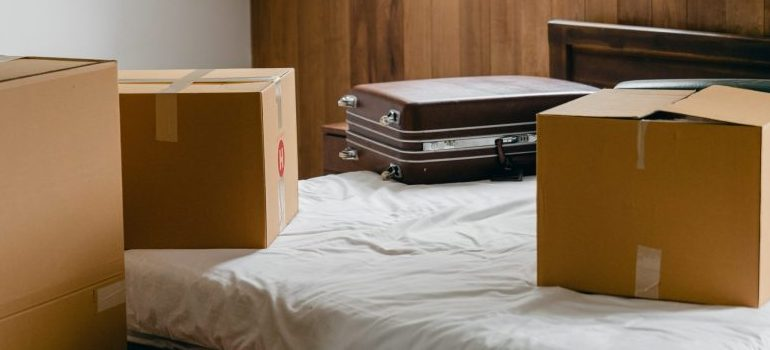 A bed with suitcases and cardboard boxes.