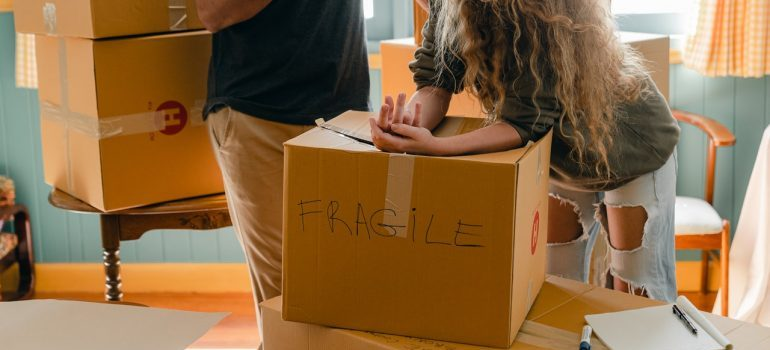 A woman leaning on a box that's labeled as fragile