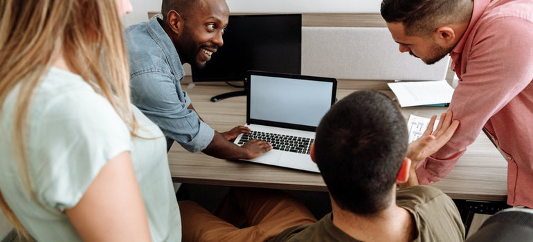 People in a meeting looking at a laptop screen, before hiring the best Caroll Garden movers.