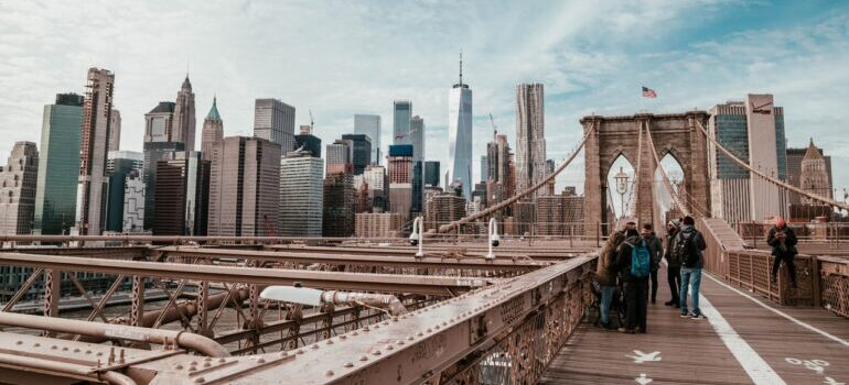 People standing on the Brooklyn Bridge, before moving from NYC to Boston.