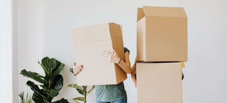 Two people standing with cardboard boxes.
