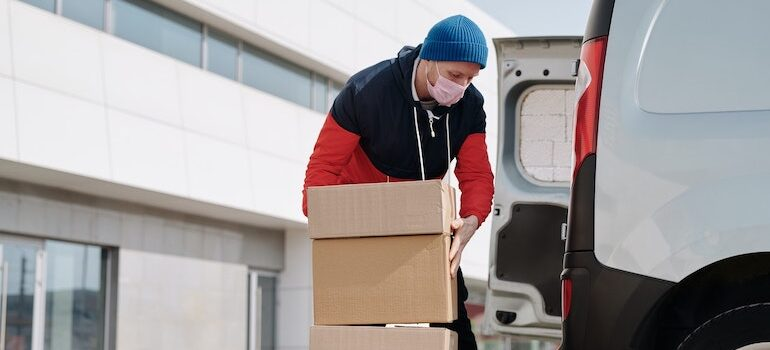 A man with a mask loading cardboard boxes into a white van.