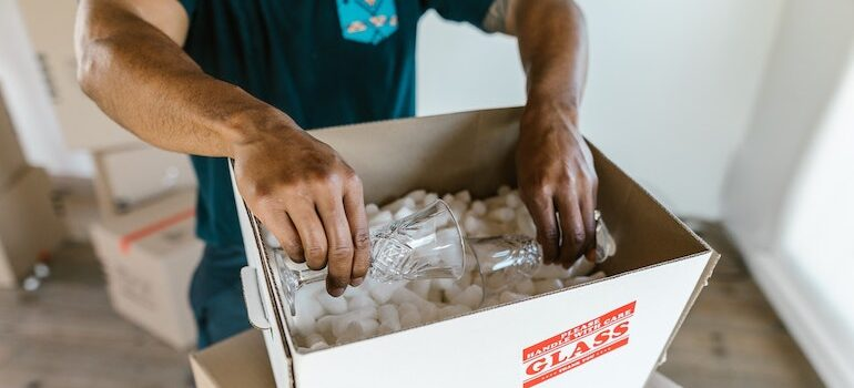 man putting glasses into a box is part of movers Crown Heights