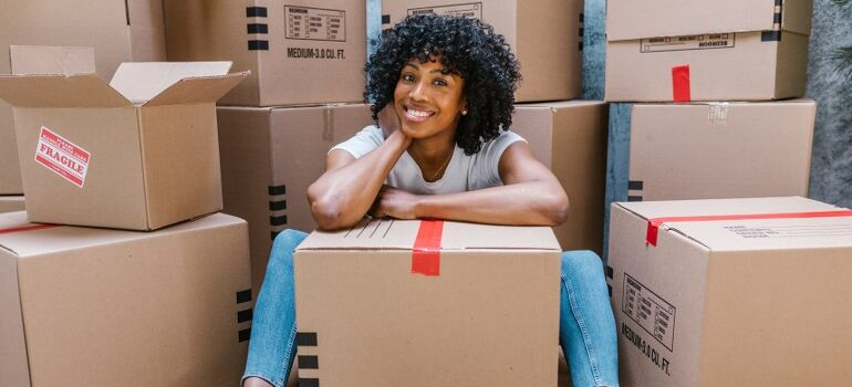 woman smiling amid cardboard moving boxes