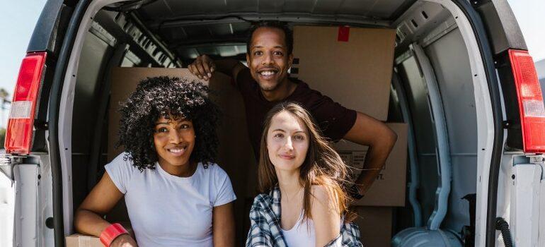 three people inside a moving van