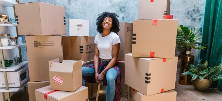 A woman surrounded by moving boxes smiling and thinking about all the reasons to hire local movers NYC residents recommend.