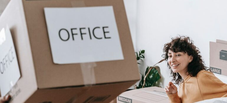 """woman looking at a cardboard box labeled """"office"""""""