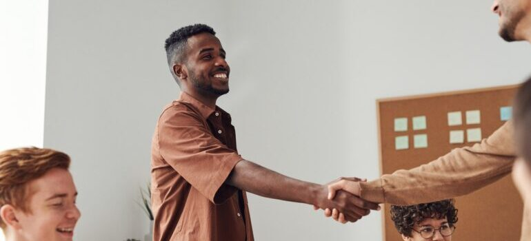 A man shaking hands with one of the Somerville NY movers