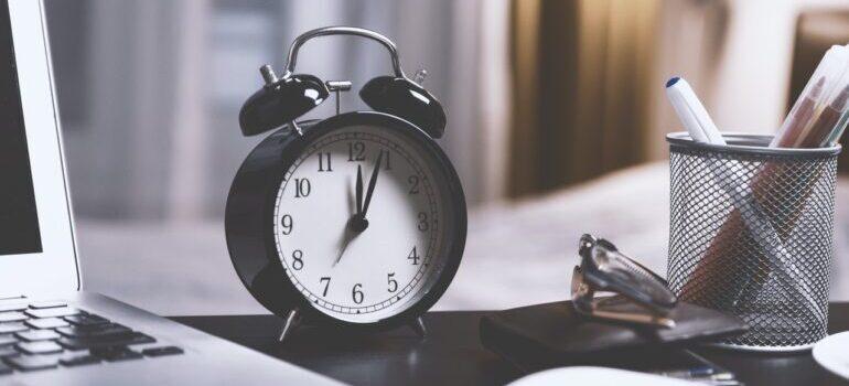A black clock on a desk