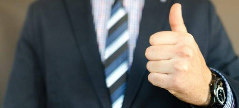 A person in a suite showing thumbs up