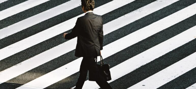 A man in suit with a suitcase crossing a street