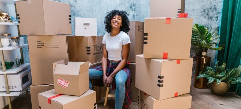 Woman smiling with boxes behind her