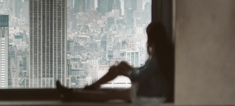 a girl sitting on the window sill looking out of the window at New York roofs